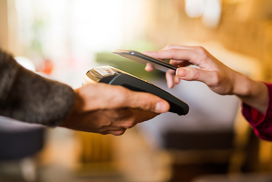 Photograph of someone using a phone to make a purchase. Someone else is assisting them by holding the payment terminal.