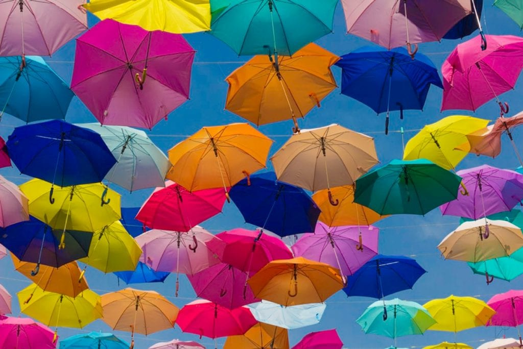 Photograph of a bunch of colourful umbrellas hanging in the sky.