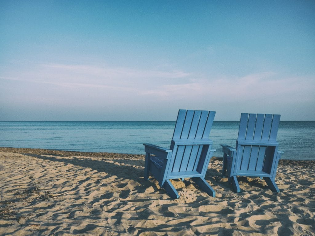 Photograph of two empty Adirondack/Muskoka chairs on a beach.