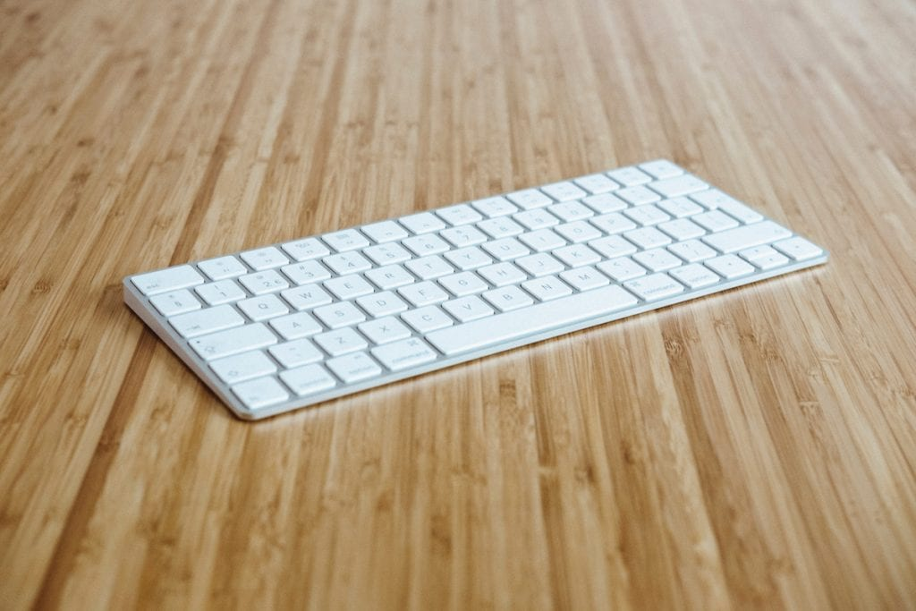 Photograph of a wireless keyboard on a wood surface.