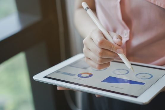 close up on businesswoman manager hand using stylus pen for writing or comment on screen dashboard tablet in meeting situation about company's performance , technology and business strategy concept