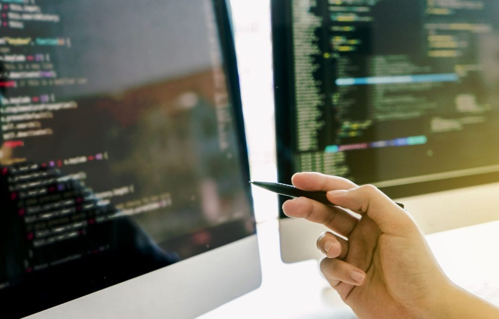 Developing programming and coding technologies working in a software engineers developing applications together in office.