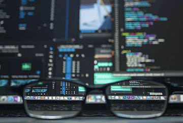 Glasses in front of code on a computer screen